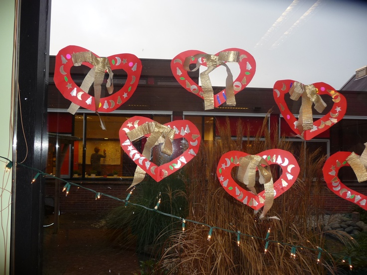 MAP: harten, versierd met plakfiguurtjes en een gouden strik. Kunnen ook ruimtelijk aan het plafond gehangen worden.