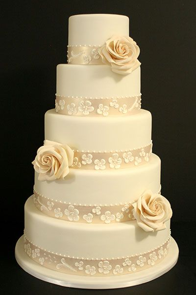 Wrap each tier in pearlized fondant, accentuated with sugar flowers.Cake by Mark Joseph Cakes