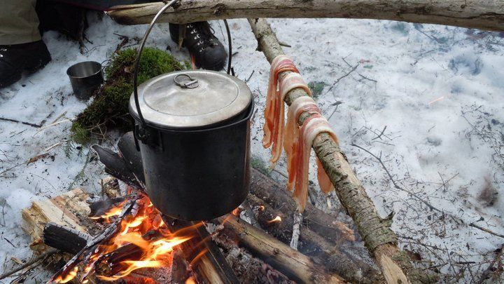 Billy can pot and bacon cooking over a camp fire. # ...