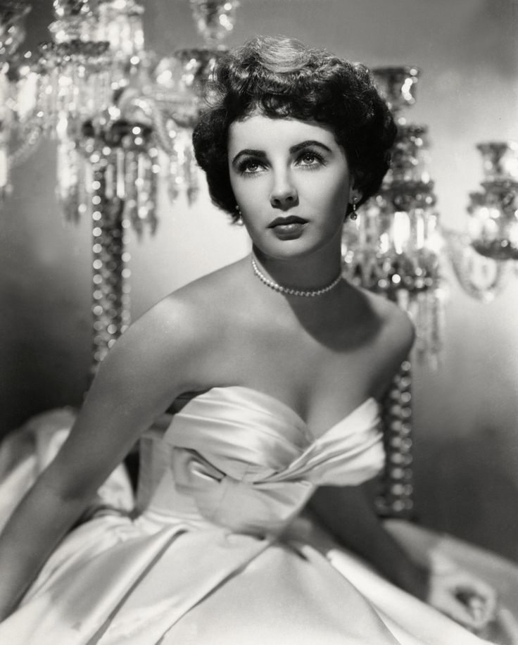 British-born American actress Elizabeth Taylor (1932 – 2011) in a white, off-the shoulder ball gown, circa 1951. Description from prodijee.com. I searched for this on bing.com/images