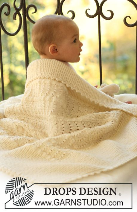 "Knitted DROPS blanket with wavy pattern in ""Merino Extra Fine""."
