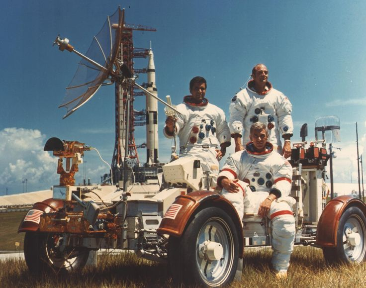 At Cape Canaveral, Apollo 17 crew in spacesuits, posing in moon rover with rocket on launchpad in background
