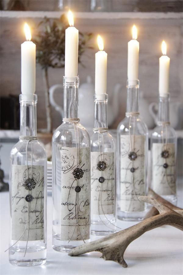 Putting a taper candle in a bottle is a dramatic centerpiece detail at weddings and events. Decorate the bottle with paper, twine, flowers or sprigs for a personalized look.  http://www.lightsforalloccasions.com/c-63-taper-stick-candles.aspx