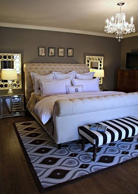Placing mirrors behind twin night-table lamps will reflect light and help brighten a room. Good idea to incorporate,  especially when choosing dark wall color.    Also, the rug positioned under the bed.