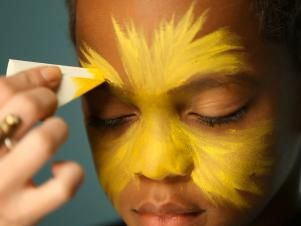 To create a base for your lion makeup, begin by dampening a sponge then picking up some of the yellow face paint. Tip: When using dry face paints, be sure to get sponge or brush wet before dipping into paint. Have child close their eyes, then apply yellow paint to the center of their face and blend out.