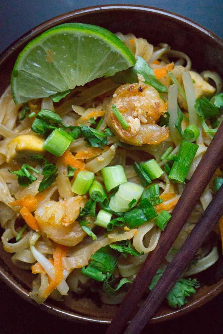 Pad Thai 1 tbsp canola oil 1 tbsp sesame or peanut oil 2 onions, sliced thinly 100g (3 ounces) extra-firm tofu, pressed and diced 6 cloves garlic ¼ tsp chili flakes 225g (½ lb) shrimp or very thinly sliced chicken or pork 1 egg 2 tsp sugar 1 tbsp fish sauce 2 tbsp oyster sauce 250g (1/2 lb) flat rice noodles (shaped more like fettuccine) 1 carrot, shredded 200g (7 oz) bean sprouts limes chopped peanuts chili flakes sugar green onions
