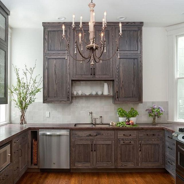 Small kitchen features a French candle chandelier illuminating dark stained  cabinets paired with a dark stained wood countertop and a gray tiled  backsplash.