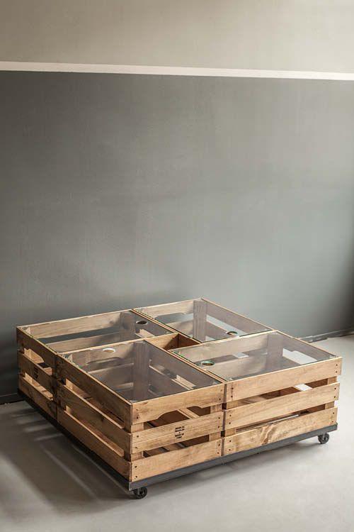 Rolltisch. Rollgestell aus schmalen Winkelstahl und schwarzen Rollen, zwei davon mit Feststellfunktion. 4 Holzkisten mit eingelegten Glasscheiben.