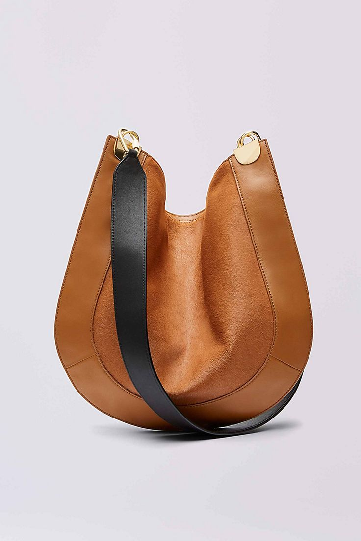 This modern crossbody satchel is an unexpected statement piece for every day. A luxurious haircalf body and soft leather border are accented with a contrast leather strap and half moon hardware. With zip top closure and detachable leather pouch.