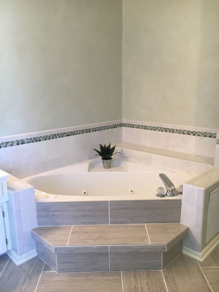 Corner bathtub with low wall and step up.