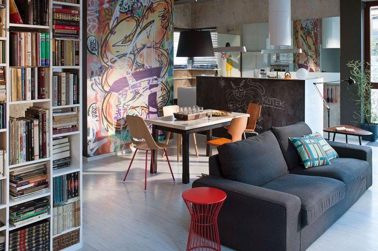 Salon z kuchnią stworzony został na bazie szarości i kolorów natury, a niezwykłego charakteru dodają mu artystyczne dekoracje ścian – tapety zrobione na zamówienie i obrazy. Aranżację wnętrza podwaja lustrzane odbicie, które wygląda niemal jak rzeczywista kontynuacja salonu z kuchnią.