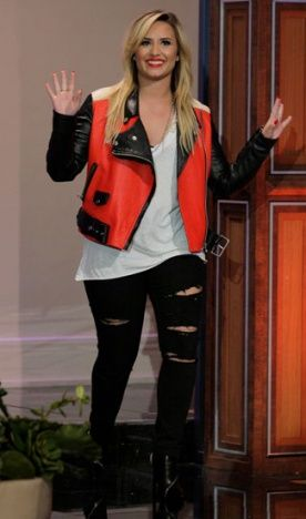 Demi Lovato combinou o jeans rasgado com t-shirt podrinha e jaqueta de couro bicolor, estilo motoqueiro.