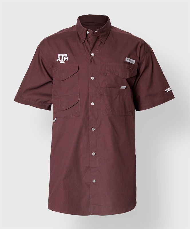 """Perfect gift for your man this Valentine's Day! This maroon fishing shirt from Columbia has a large white block ATM on the chest. The front has 4 pockets for various fishing gear and a pole tab. The left sleeve is embroidered with text that reads """"Texas A&M"""""""
