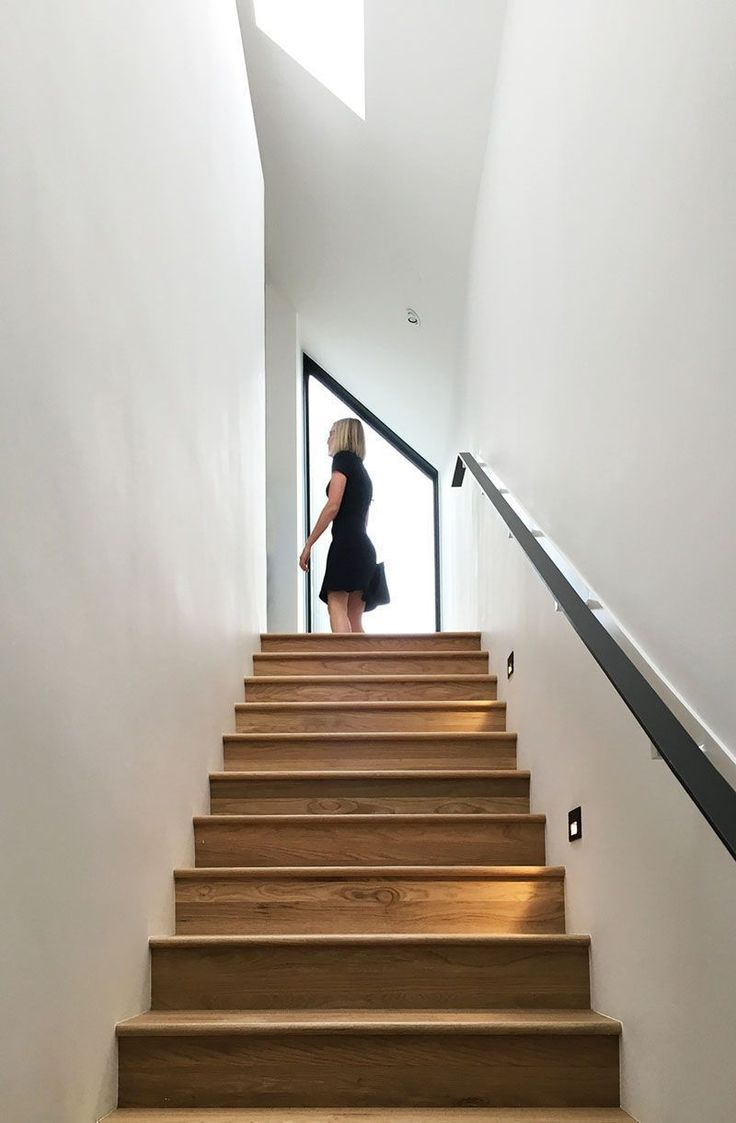 Connecting the garage and the upper floor of this modern house, is a light-filled stairwell with wooden stairs and a minimalist black handrail. #WoodStairs #StairDesign