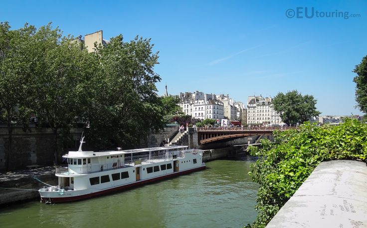 A boat passing on the River Seine and under the Pont au Double, connecting to an island at the centre of Paris.  More information and details at www.eutouring.com/images_pont_au_double.html
