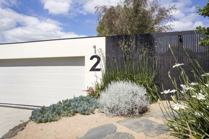 a front path set with free-form bluestone pavers is lined by drought tolerant plants including Anigozanthos (commonly known as kangaroo paw), a silver bush of Leucophyta brownii, and Dieties Iridiodies (African iris).