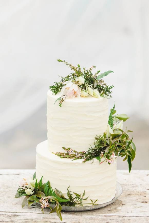 "It's become very popular to go with a ""boho chic"" or ""woodland glam"" wedding cake. But we love the more stripped-down version, representing the heart of bohemian weddings. The cake above features tiny sprigs of greenery and swirls of ivory buttercream."