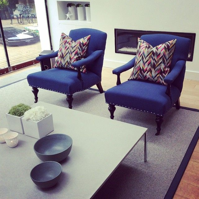 Interior design project by lathamshome.com Blue armchairs, geometric cushions, bordered rug, concrete coffee table