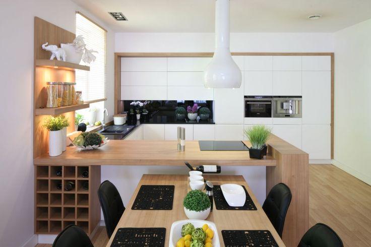 W otwartej kuchni wysoka zabudowa ulokowana została na całej ścianie. Ujęta w eleganckie, drewniane ramy idealnie koresponduje z przestronnym półwyspem. Projekt Małgorzata Błaszczak. Fot. Bartosz Jarosz.