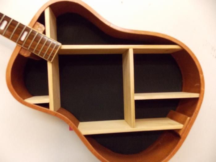 Acoustic Guitar made into wall shelf I would of course only use a really junky guitar, or one that was beyond salvage.