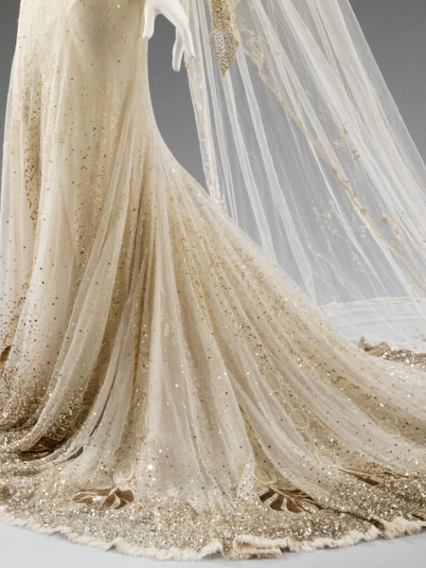 Wedding Dress and veil by John Galliano, worn by Kate Moss, 2011 - The dress's skirt and train are embroidered in gold sequins and pearls, which build into phoenix feathers. © Victoria and Albert Museum, London