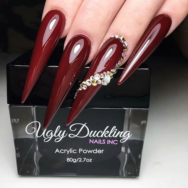 Extreme stiletto shaped nails with burgundy gel polish and gold light yellow rhinestone swirl art design on ring finger. Ugly Duckling sculpted acrylic and gel polish #112 with No Wipe Topcoat by Ugly Duckling Master Educator @amyduclosnails  Ugly Duckling Nails page is dedicated to promoting quality, inspirational nails. Tag us and mention what Ugly Duckling pr