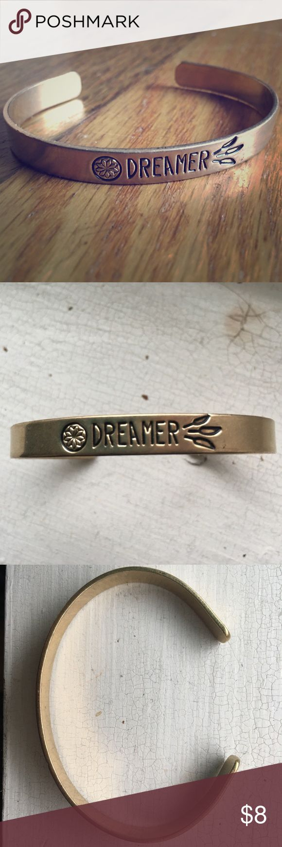 """Dreamer dreamcatcher cuff bracelet Narrow gold color cuff bracelet """"dreamer"""" with dream catcher etched. Small mark from the adhesive tag that was on it, haven't been able to get if off but isn't too noticeable. (See photos). Really cute stacked with other bracelets, I wore it once or twice with friendship braided bracelets. Jewelry Bracelets"""