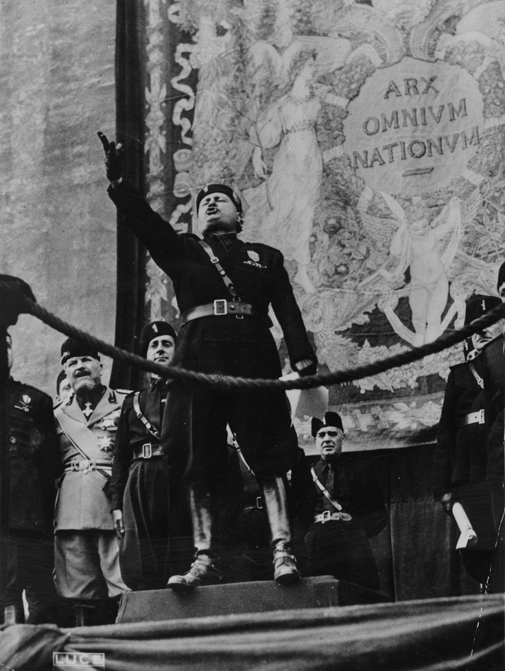"Mussolini was always a spectacle when he spoke to the people. Hyperbole, gesticulations, and fanfare posturing were among his strongest points. The inscription in Latin behind him reads: ""Lord of All Nations."""