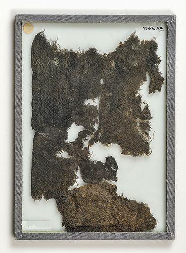 Wool textile fragments. Due to decomposition, textile fragments are rarely found. Grave find, Björkö, Adelsö, Uppland, Sweden. SHM 34000:Bj. 597. In the Historiska Museet, Stockholm.