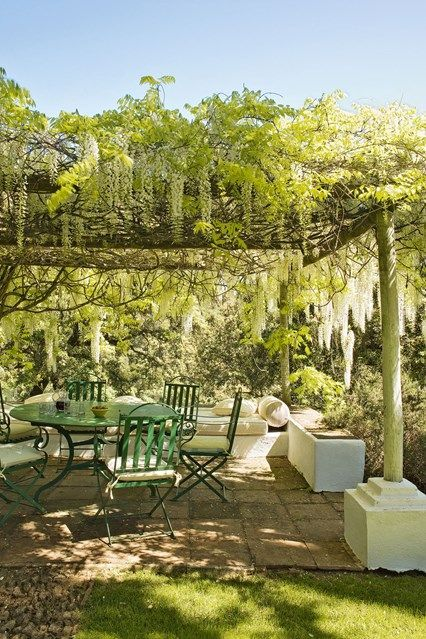 The Pergola in Dream Spanish Home Traditional Farmhouse. The pergola outside is dripping in wisteria, below is a sitting area with wrought iron garden furniture.