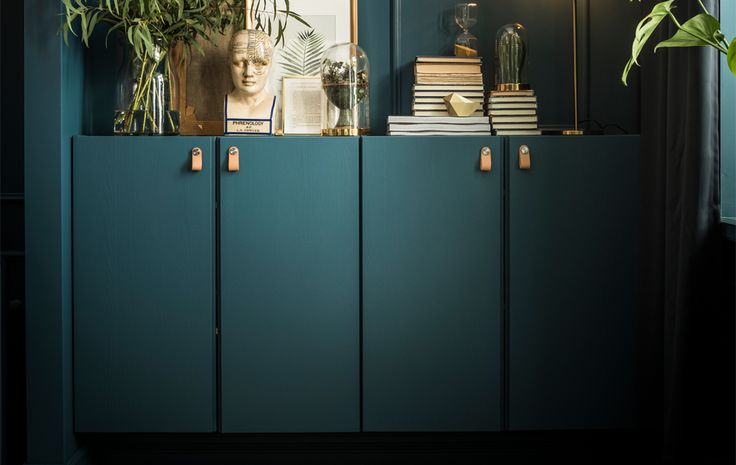Two IVAR cabinets are custom painted in the same shade as the walls and hold books, artwork, plants, and a lamp on top.