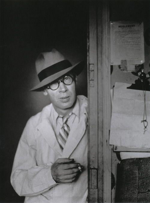 Henry Miller au chapeau dans l'embrasure de la porte  [Henry Miller Standing in a Doorway Wearing a Hat]  Hôtel des Terrasses, Paris, circa 1931-1932  From Brassaï, Paris