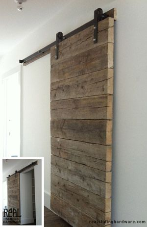 Salvaged barn door creates a feature - hung on sliding door track system