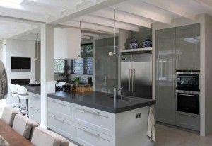 Een jaren 30 keuken. klassieke paneeldeuren en vooral opvallen en mooi zijn de muurtjes tussen de kasten. Het kookeiland met grote grepen.