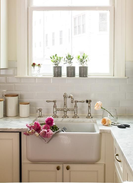Cottage kitchen features ivory shaker cabinets paired with white marble countertops framing a small farmhouse sink with a deck mount bridge faucet under window sill lined with potted herbs framed by white beveled subway tiled backsplash.