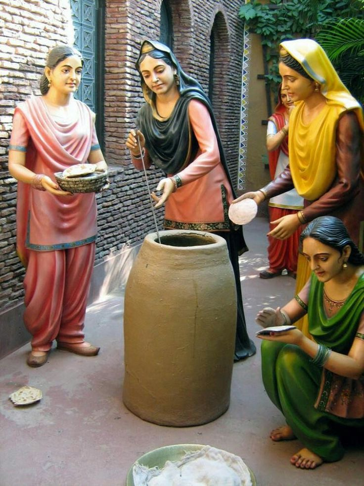Women from neighborhood making tandoori naan in a tandoor(mud oven fueled with wood) .Punjabi Culture Art Design Punjab Pakistan