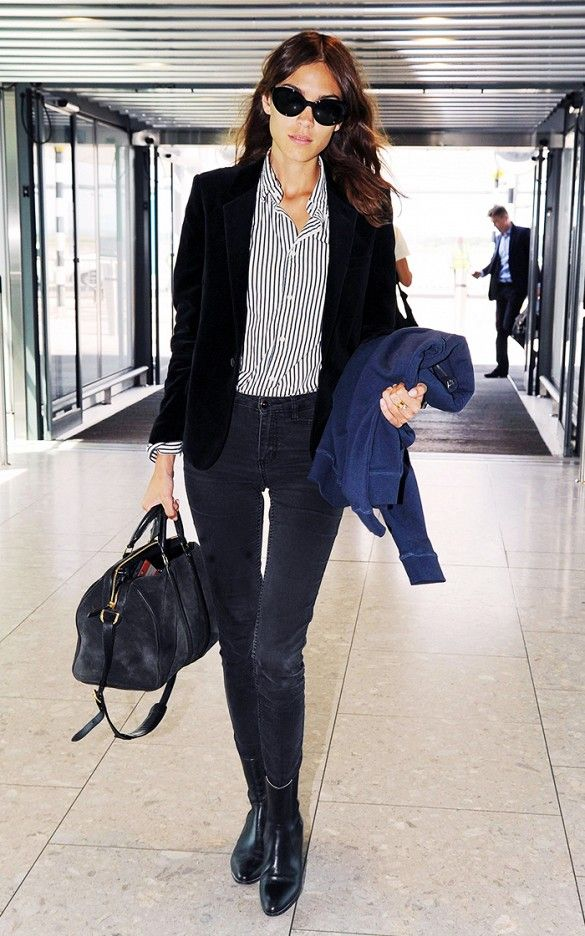 Alexa Chung wears a striped button-down shirt with a blazer, skinny jeans, ankle boots, a satchel bag, and cat-eye sunglasses
