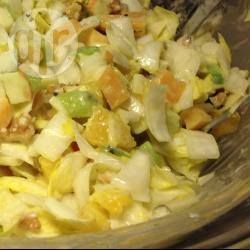 Foto recept: Frisse witlofsalade  ngrediënten  Porties: 3  4 stronken witlof flinke handvol gepelde walnoten light dressing (Becel, pot) 1 kiwi 1 halve appel 1 sinaasappel stuk belegen of oude kaas, in blokjes