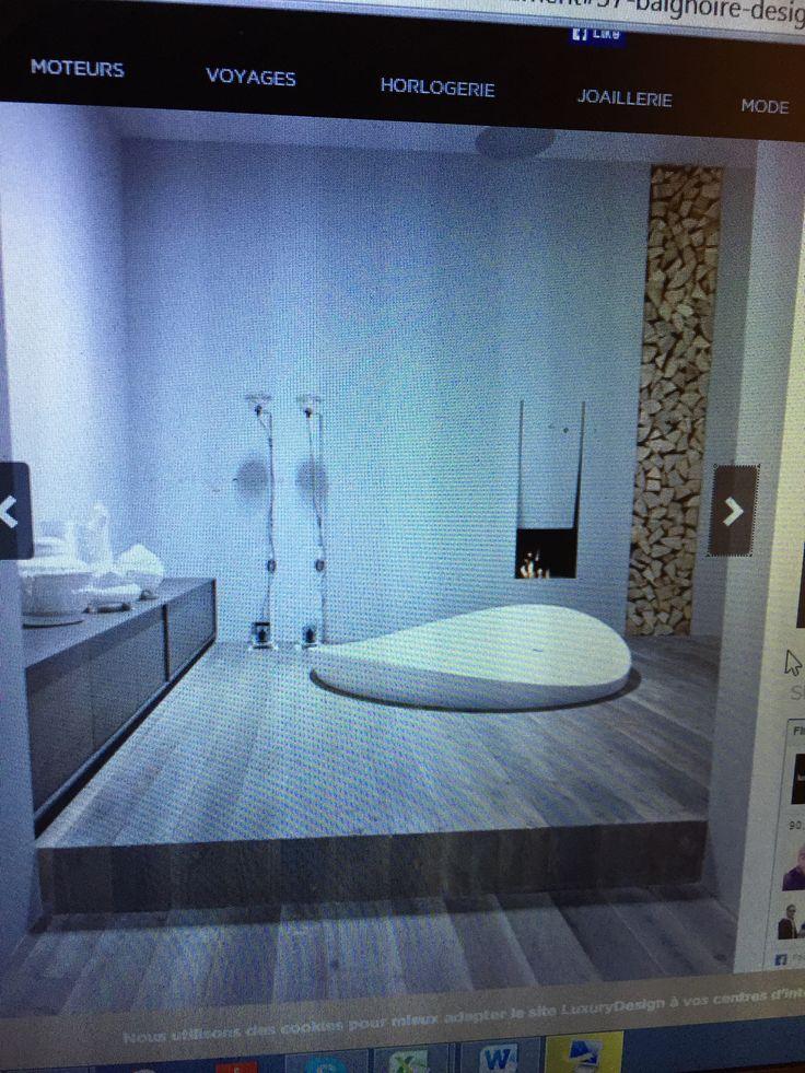La salle de bain la plus sublime : bois, baignoire arrondie à moitié apparente, cheminée, buches, deux pommeaux de douche