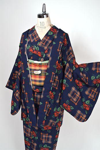 こっくりと深いネイビーブルーをベースに、椿の花と井筒絣が市松のようなモダンパターンを描き出すウールのアンサンブル(着物と羽織のセット)です。