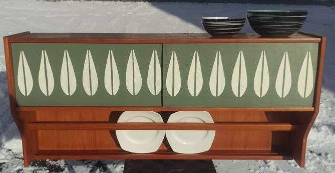 Tidenes tøffeste teak-møbel for kjøkkenveggen, eller kanskje til veggen i retro-spisestua En teak vegghylle med skap og tallerkenhylle Grønne skyvedører med det kjente lotus-mønsteret Unikt møbel som ingen andre har maken til Designet og produsert av velrenomerte Elegante møbler, Vegsund Skyvedører som gjør at du har enkel tilgang til begge rommene med enkle håndbevegelser Og bonusen er at alt ...