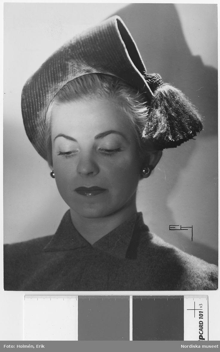 Av Claude S:t Cyr, Paris, 1949. Porträtt av modell i guldbrun, helstickad sammetshatt med silkestofs, samt örhängen. Fotograf: Erik Holmén