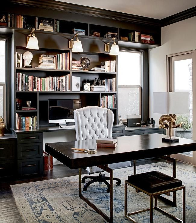 Ivory walls lined with black crown molding beautifully complement this contemporary home office boasting a black leather stool is positioned on a gold and blue vintage rug in front of a brass base desk with a black top also seating a white tufted wingback desk chair.