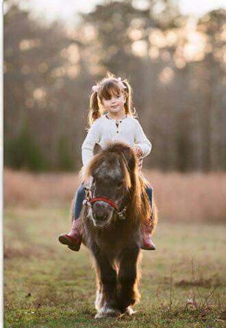 Little girl riding miniature pony