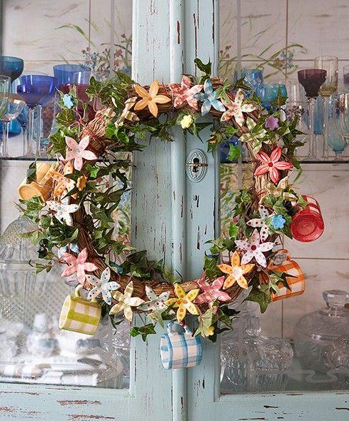 Laços, flores, figuras de pássaros, minixícaras e ícones religiosos decoram guirlandas feitas para usar o ano inteiro