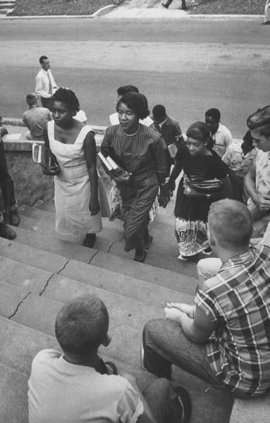 Seven African American teens walking the steps to the school, while the white students are watching on during the demonstration regarding school integration. 1956.
