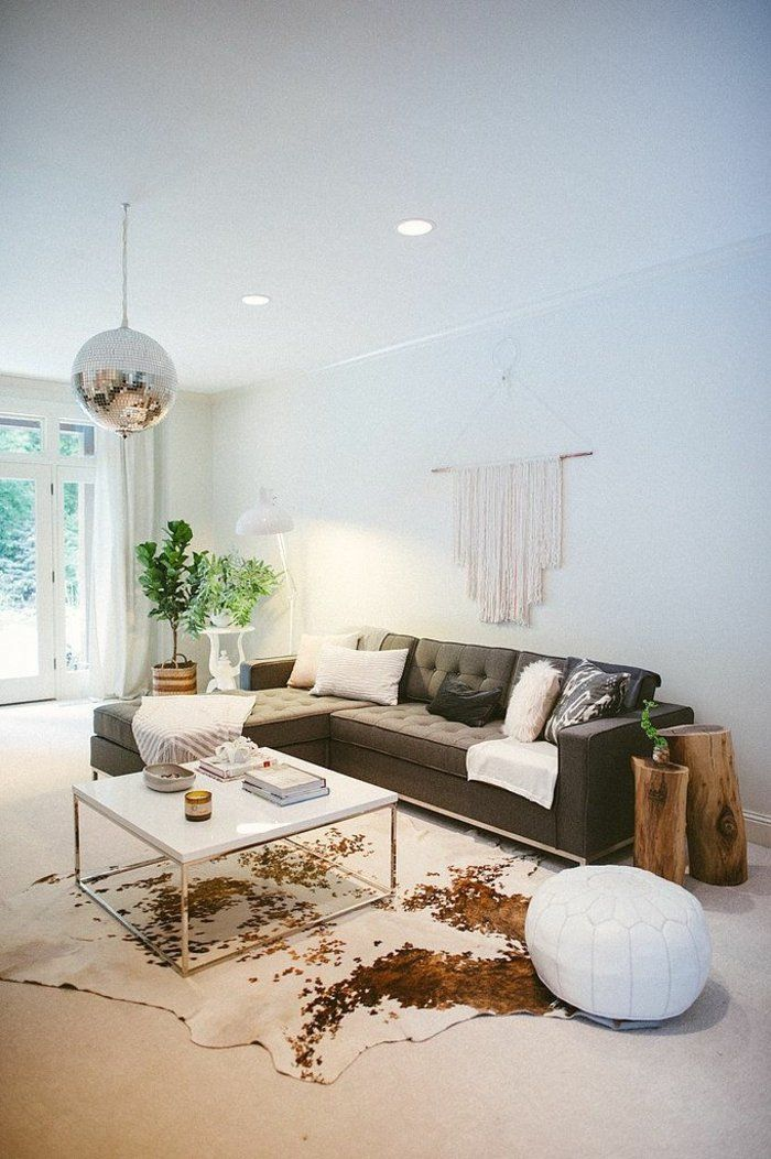 canapé vert, tapis en peau, lustre boule disco, salon moderne, mur blanc, plafond blanc