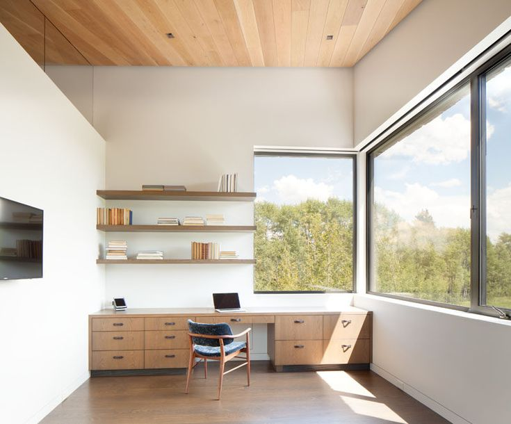 This modern home office has a long desk that has plenty of storage, and simple wood shelving installed above it. #HomeOffice