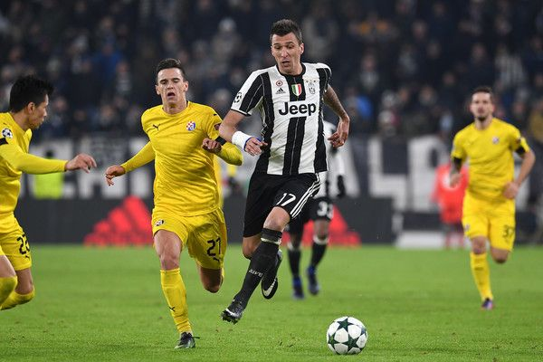 Mario Mandzukic (R) of Juventus is challenged by Nikola Moro of GNK Dinamo Zagreb during the UEFA Champions League Group H match between Juventus and GNK Dinamo Zagreb at Juventus Stadium on December 7, 2016 in Turin.