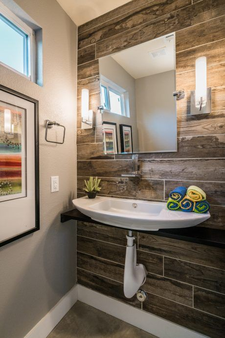 This eclectic house has a fun bathroom. I like thrust of the feature wall with textured ceramic tiles which look like wood. Nice use of color in the towels and print on the adjoining wall.